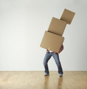 A person carrying boxes and thinking about HRA moving services.