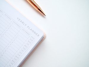 There is a planner and a pen, something you will need when you are hiring NYC movers in the summer.