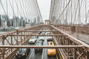 Cars on the Brooklyn Bridge driving to the the poshest neighborhoods