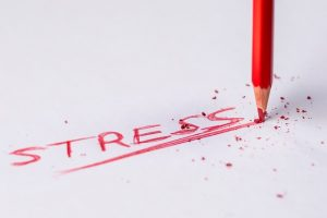 The word 'stress' written on a piece of paper in red signifying how stress is a part of moving to a smaller apartment in Queens.