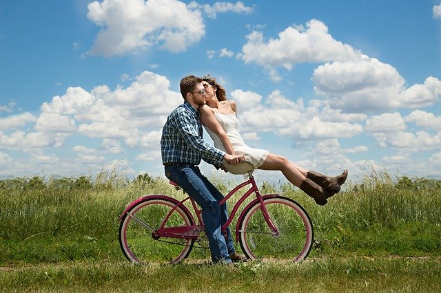 A couple posing on a red bike and talking about creative ideas for storing your bicycle.