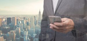 A businessman looking at his phone in the foreground and Manhattan view in the background..